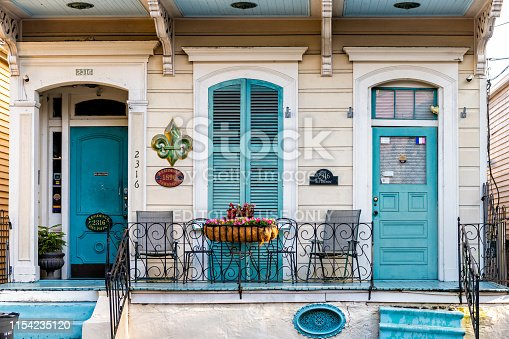 New Orleans, USA - April 22, 2018: Old Dauphine street district in Louisiana famous town with blue painted house wall shutters colorful entrance building