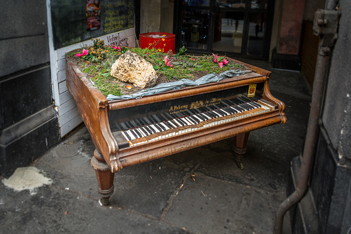 Old decorated piano abandoned on the side of the street near Budapest main station, December-23-2016