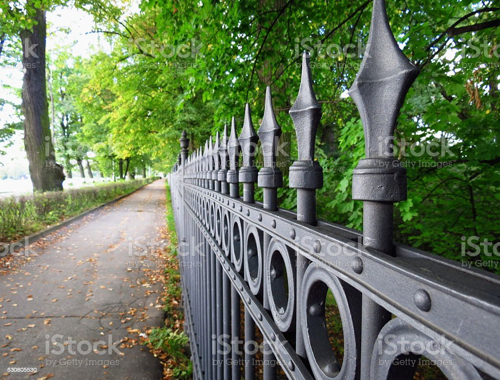 Old decorative iron fence in morning light stock photo
