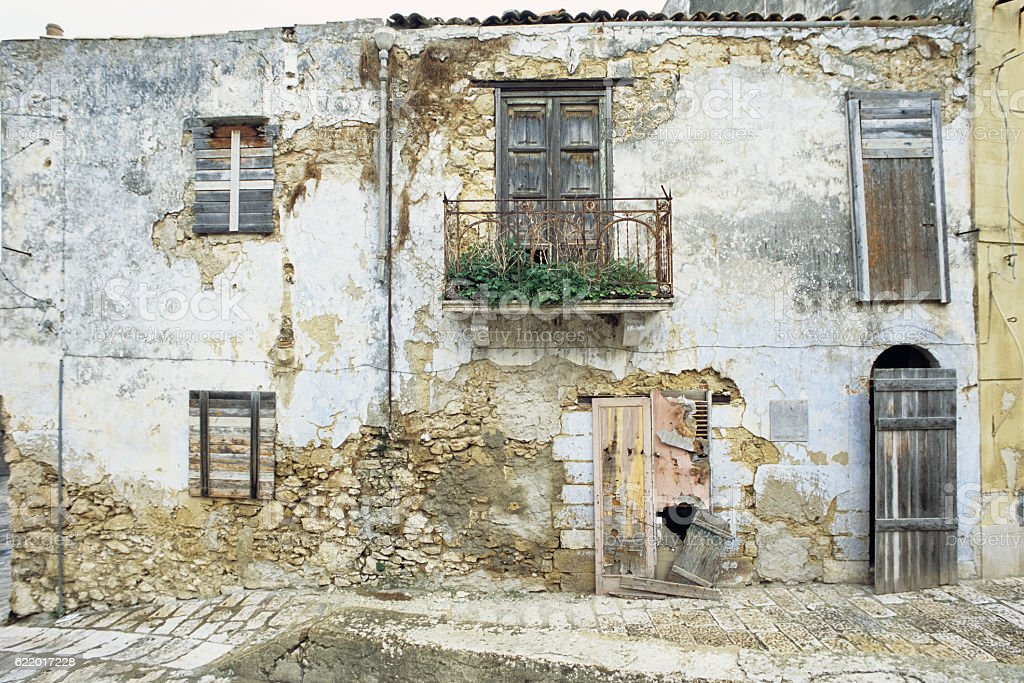 Old decrepit house facade, weathered stock photo
