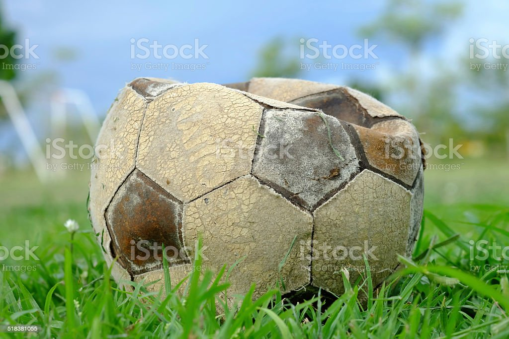 old deflated soccer ball, old deflated football on the ground stock photo