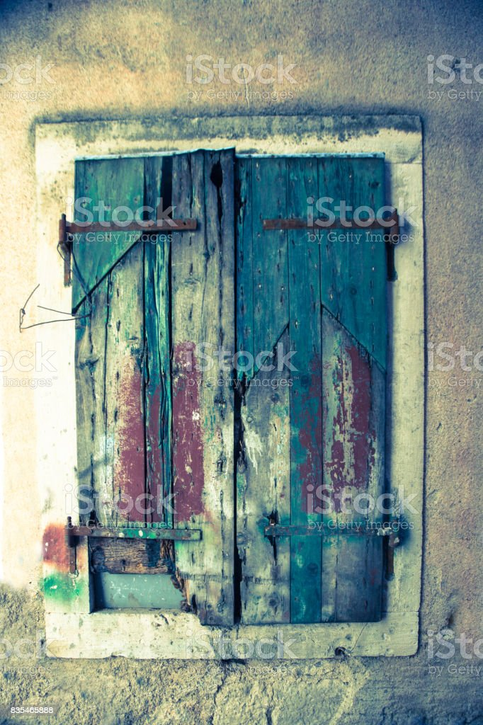 Old delapidated, grunge painted window shutter in the town of Kotor in Montenegro stock photo