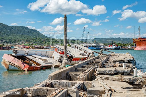 Old rusty ruined caribbean port before reconstruction, sunk ship, Puerto Plata harbor, Dominican Republic