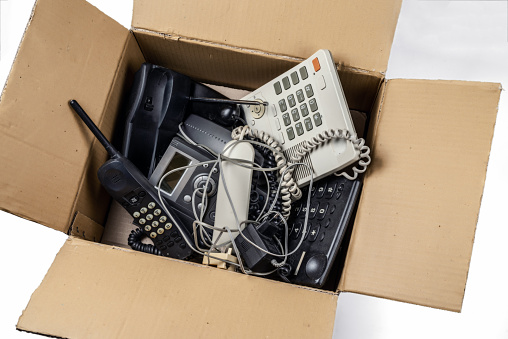 Old desk phones in a cardboard box. On a white background.