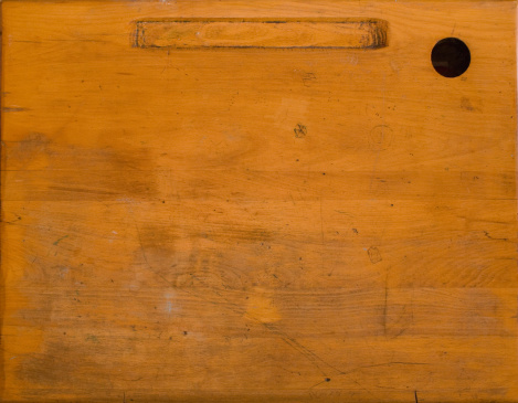 A beat up surface of an old wooden school desk.