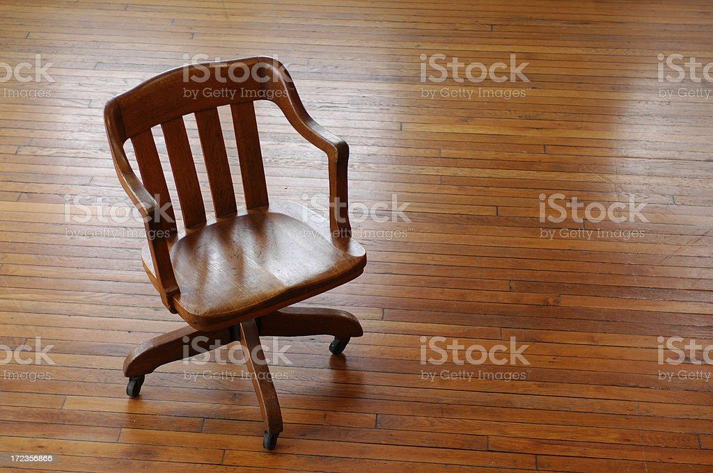 Old deskchair on wood floor royalty-free stock photo