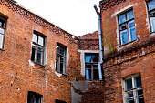 Facade of old abandoned brick house. Windows divided by white squares.