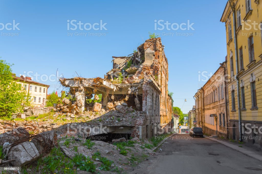 Old destroyed houses of brick with windows, overgrown with plants on street city. stock photo
