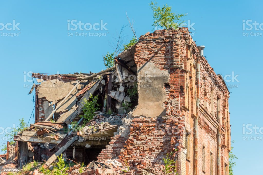 Old destroyed houses of brick with windows, overgrown with plants. stock photo