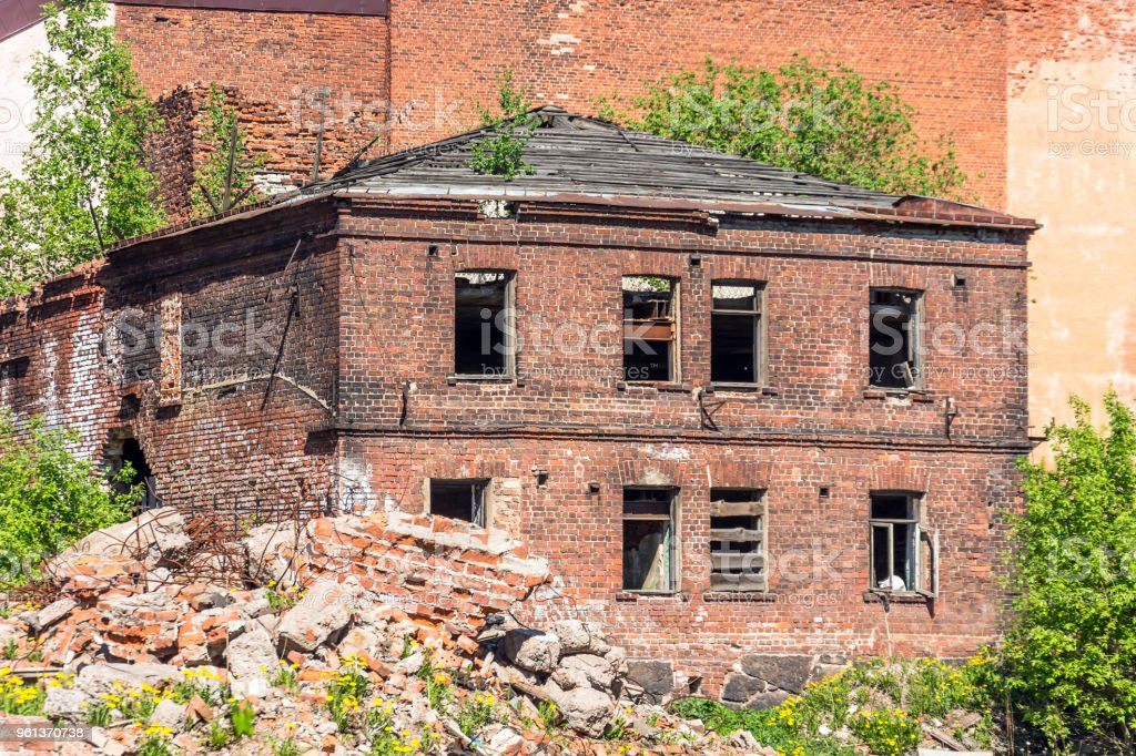 Old destroyed houses of brick with windows wall, around the ruins of the ruined city district. stock photo