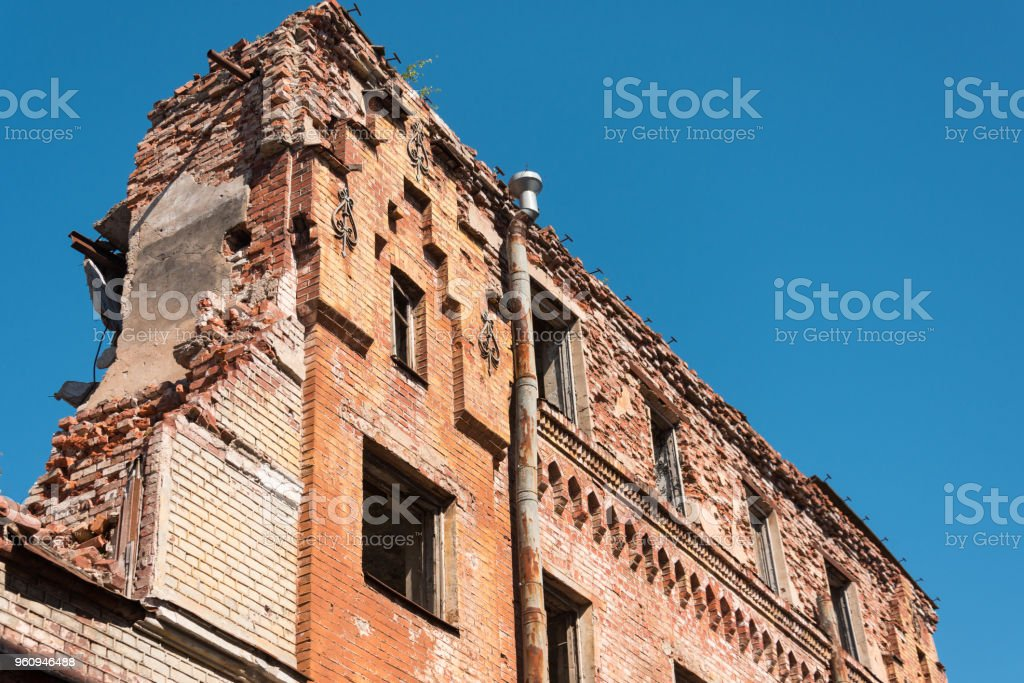 Old destroyed houses of brick with windows, wall. stock photo