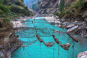 Old destroyed suspension bridge over the stormy mountain river in the Himalayas, Nepal.