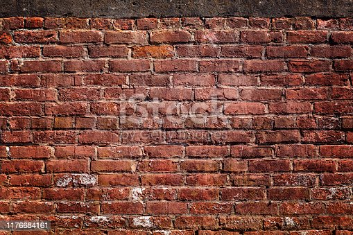 Old deteriorating Red brick wall, concrete on top, no people with copy space, vignette