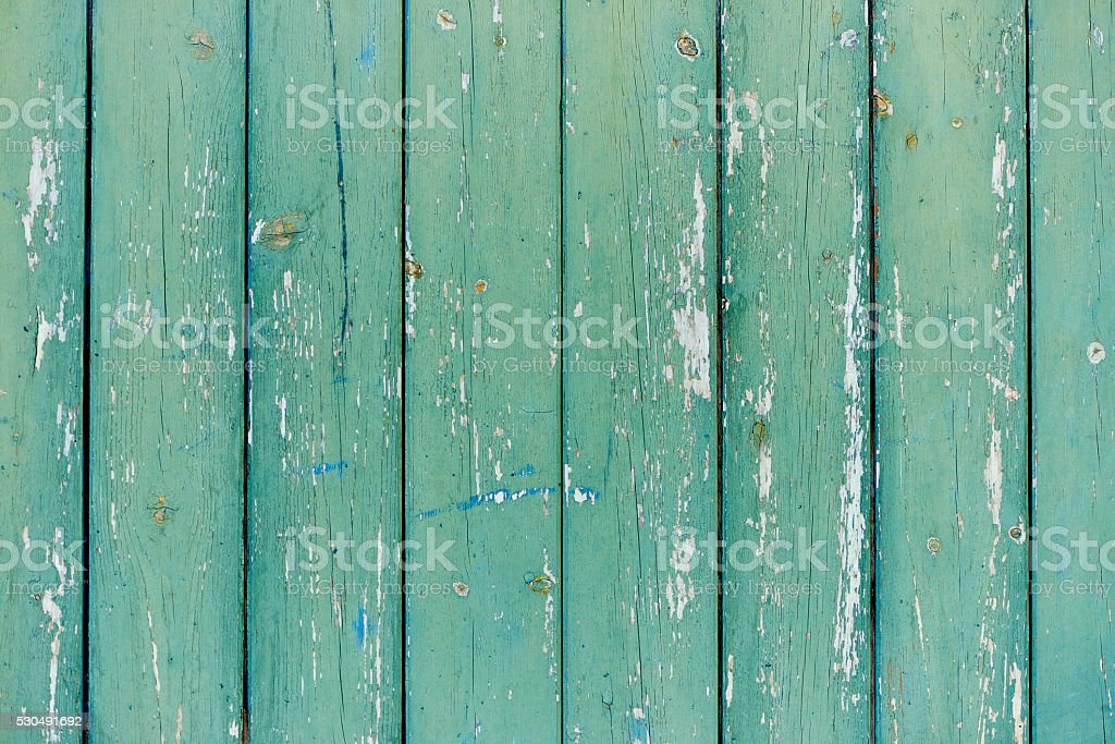 Old devastated wood wall faded light green paint peeling stock photo