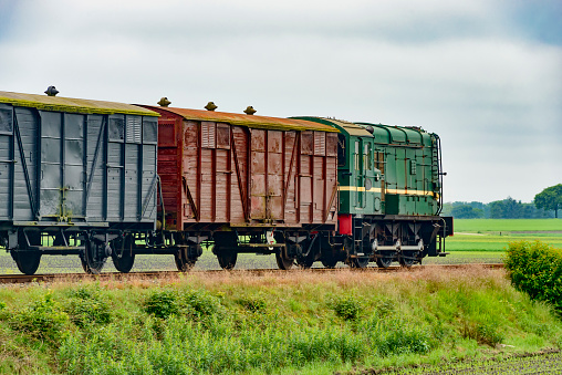 Old diesel freight train pulling various railroad cars in the countryside.