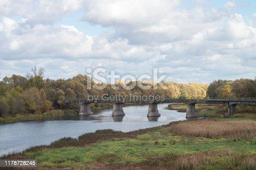 Old dilapidated bridge over the autumn Russian river Khoper.
