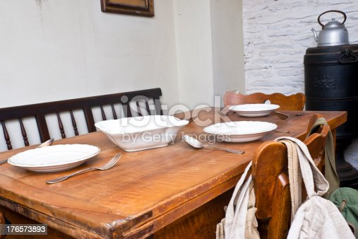 Old farmhouse dining table with an iron stove and a tea kettle in Background. South Tyrol, traditional dining table of forset workers with dishes and silverware.