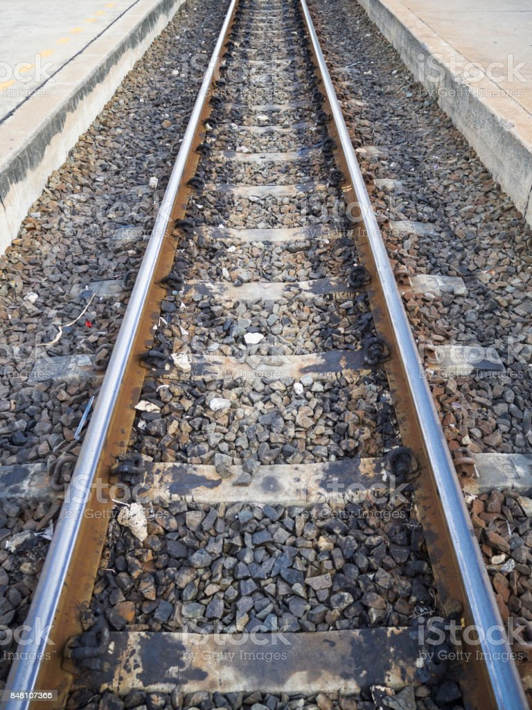 Old, dirty and rusty railway on concrete sleepers and gravel with oil staines, little gabages in rural regional. Railway between concrete pavement with yellow dashed line stock photo