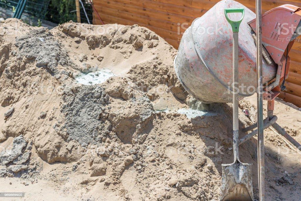 Viejo sucio hormigonera cerca de montón de arena en sitio de construcción pequeña. Obra pequeña portátil cemento mezcladora en casa - foto de stock