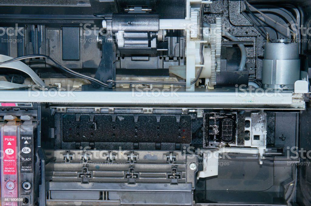 Old, dirty, disassembled ink jet printer. View of internal parts.