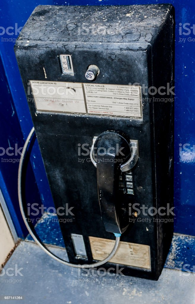 Old dirty dusty coin operated pay telephone in an open booth stock photo