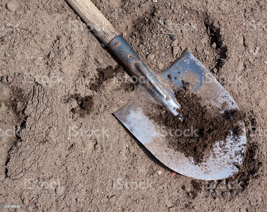Old dirty shovel on the dry ground stock photo