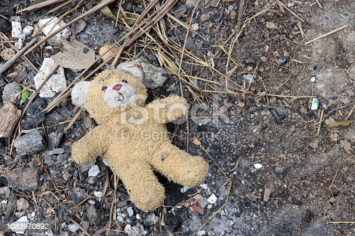 istock Old dirty teddy bear neglected on the ground soil. End of childhood. 1083970892