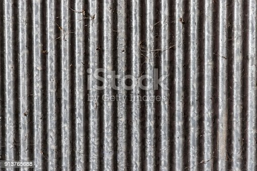 istock Old dirty zinc fence and spider web Light on left 913765688