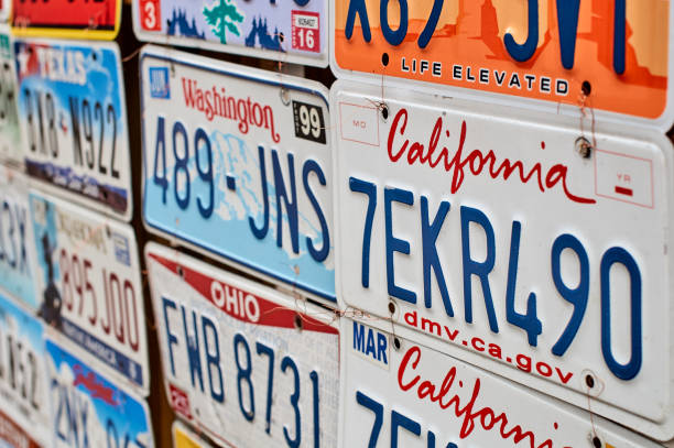 Old discontinued car license plates or vehicle registration numbers from different USA states such as California, Washington, Ohio, Texas. stock photo