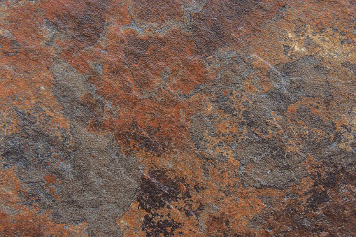 Old Distressed Brown Terracotta Copper Rusty Stone Background with Rough Texture Multicolored Inclusions. Stained Gradient Coarse Grainy Surface. Wallpaper