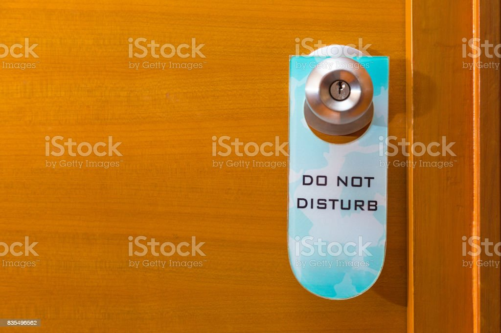 old Do Not Disturb sign tag haning on metal door knob, concept of needing privacy, room for text or copyspace stock photo