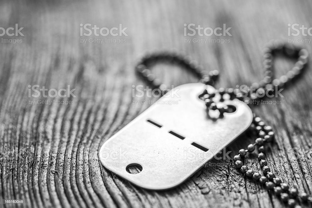 Old dog tag with blank space on wooden background stock photo
