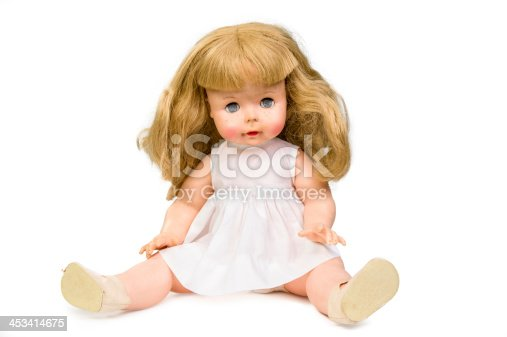 A doll from the 1960s with long blonde hair and a white dress and shoes isolated on white