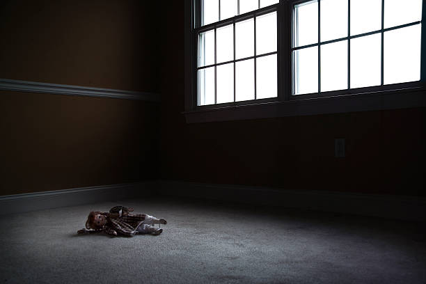 Old Doll Sitting in Empty, Dark Room stock photo