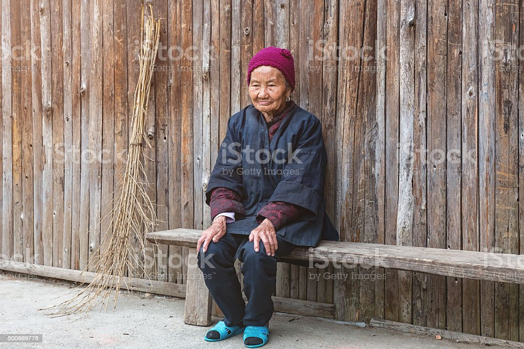 Awe Inspiring Old Dong People Minority Woman Sitting On Wooden Bench Stock Bralicious Painted Fabric Chair Ideas Braliciousco