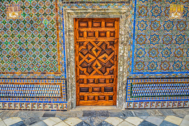 Old door and exquisite tile work Seville, Spain - August 12, 2015: Old door and exquisite tile work. Photo taken at the Casa de Pilatos during the day and contains no people. alcazar palace stock pictures, royalty-free photos & images