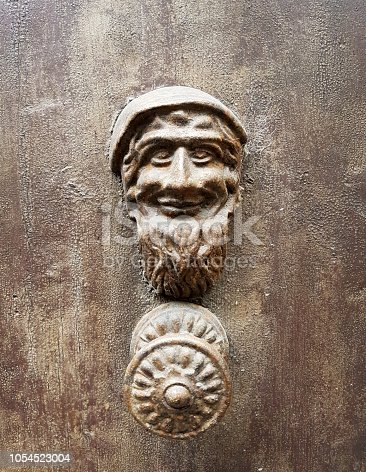worn old door with handle made from a small antique gnome in burnished metal
