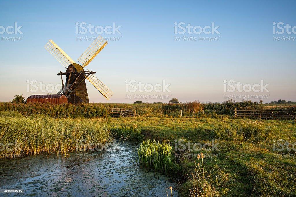Old drainage windpump windmill in English countryside landscape stock photo