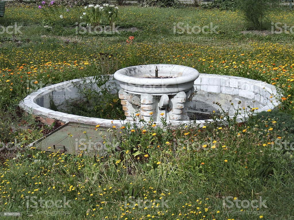 Old dry fountain in unattended garden royalty-free stock photo