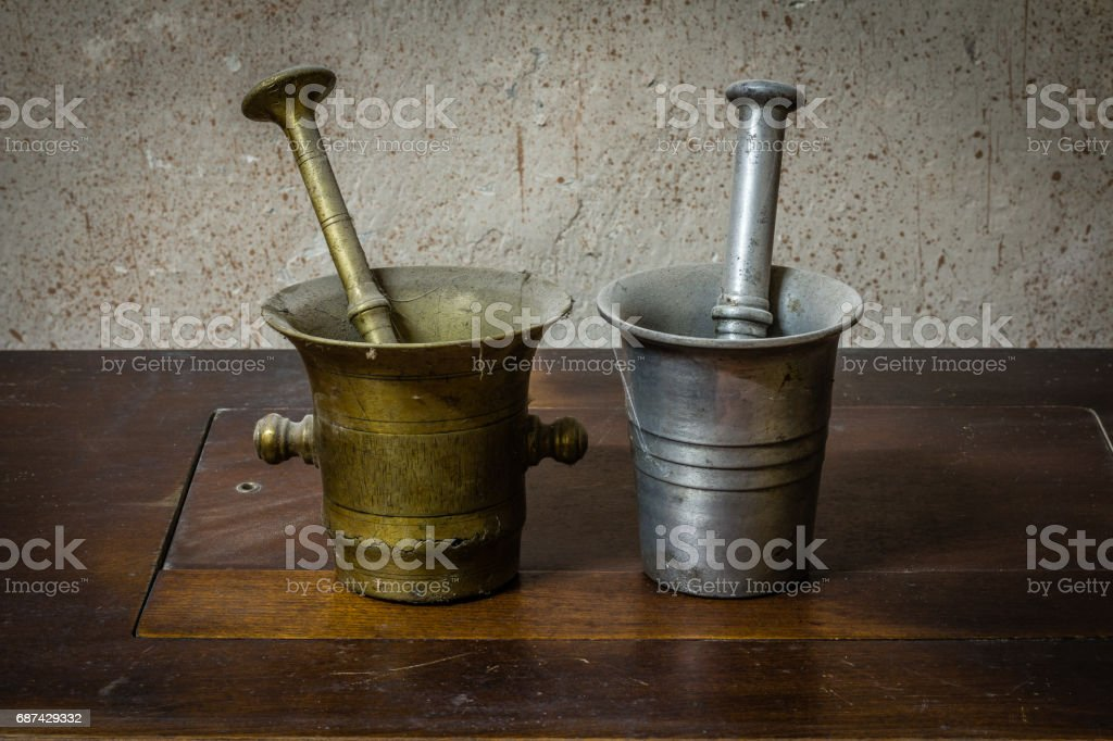 2 Old dusty bronze mortar with pestle on wooden table stock photo