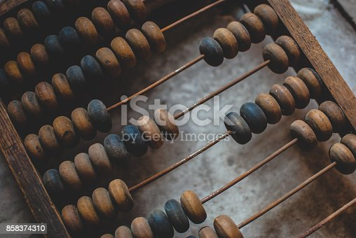 Old dusty wooden abacus laying on the dusty floor of the storage. Closeup