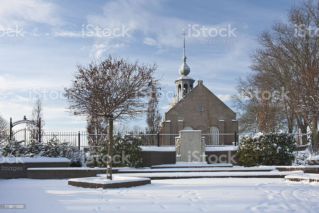 Old Dutch church with graveyard in winter royalty-free stock photo