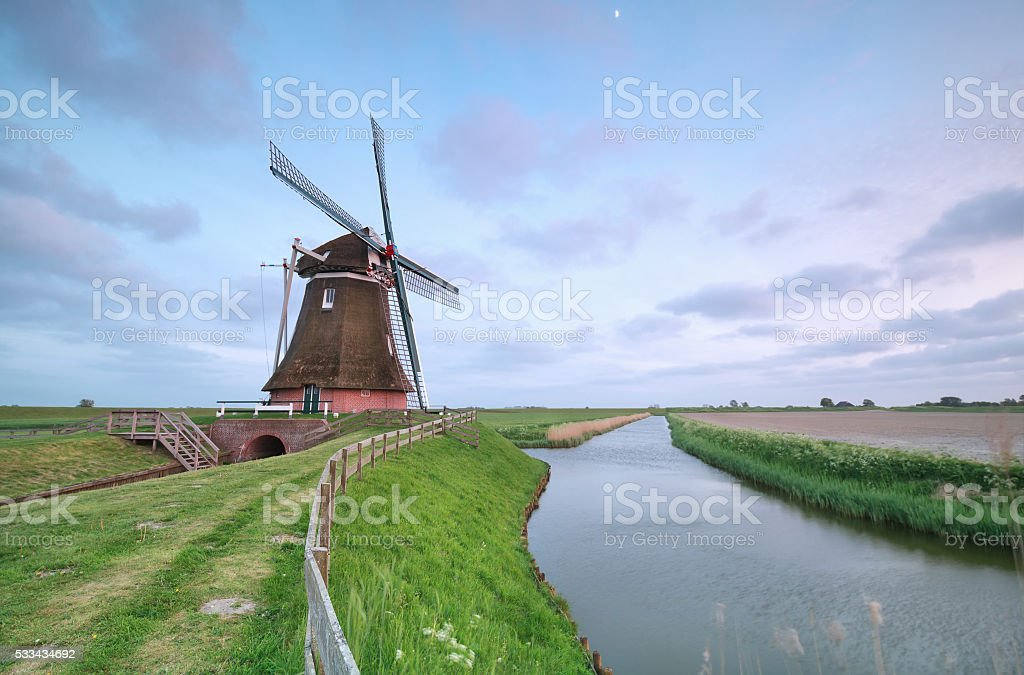 old Dutch windmill by canal stock photo