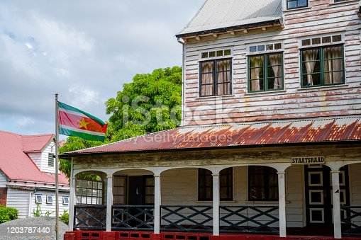 Old dutch-colonial style building in Paramaribo with the flag of Suriname
