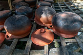 Old earthenware pots with burnt black bottoms lying upside-down on bamboo platform in a rural village in Chiang Mai.