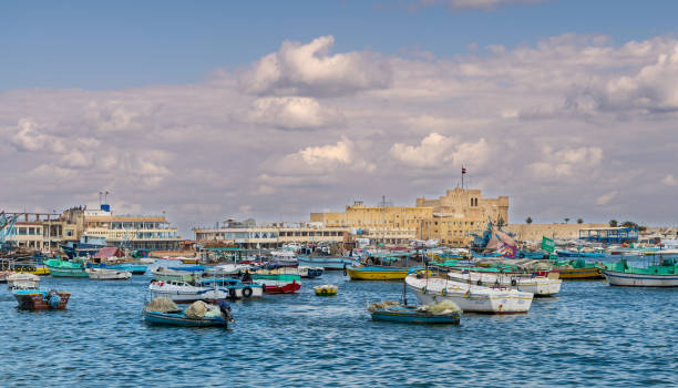 Old east harbor of Alexandria city with fishing boats in the foreground and the Citadel of Qaitbay in the background, Egypt stock photo