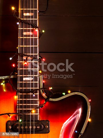 istock Old electric guitar with a lighted garland on a dark background. Greeting, Christmas, New Year greeting card. Copy space. 876579980