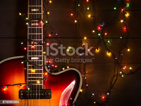 istock Old electric guitar with a lighted garland on a dark background. Greeting, Christmas, New Year greeting card. Copy space. 876580304