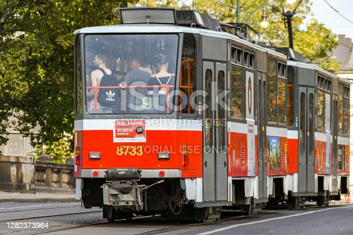 Prague, Czech Republic - August 2018: One of Prague's older electric trams on a street near the city centre. People are standing in the carriages.