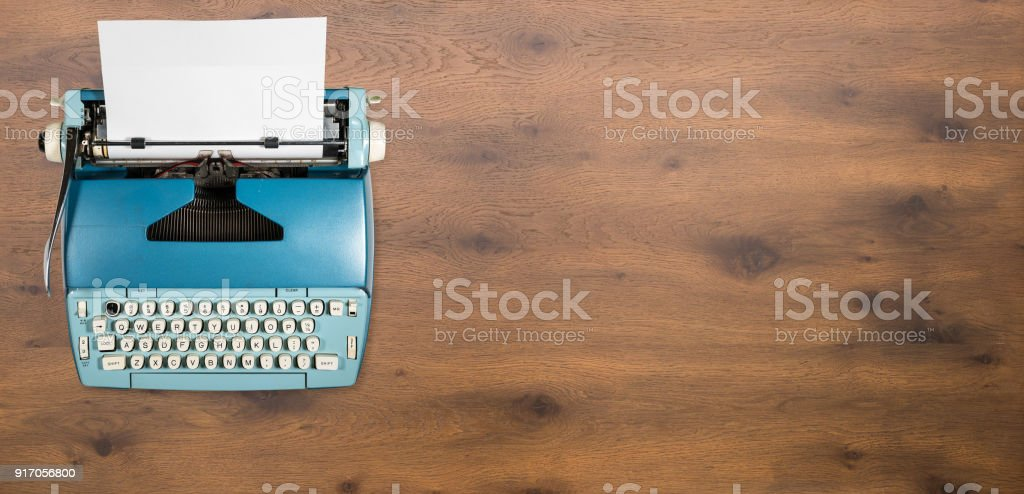 Old electric typewriter on wood background stock photo